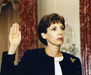 Ambassador Prudence Bushnell with her right hand raised, taking the oath of office as Ambassador to Kenya