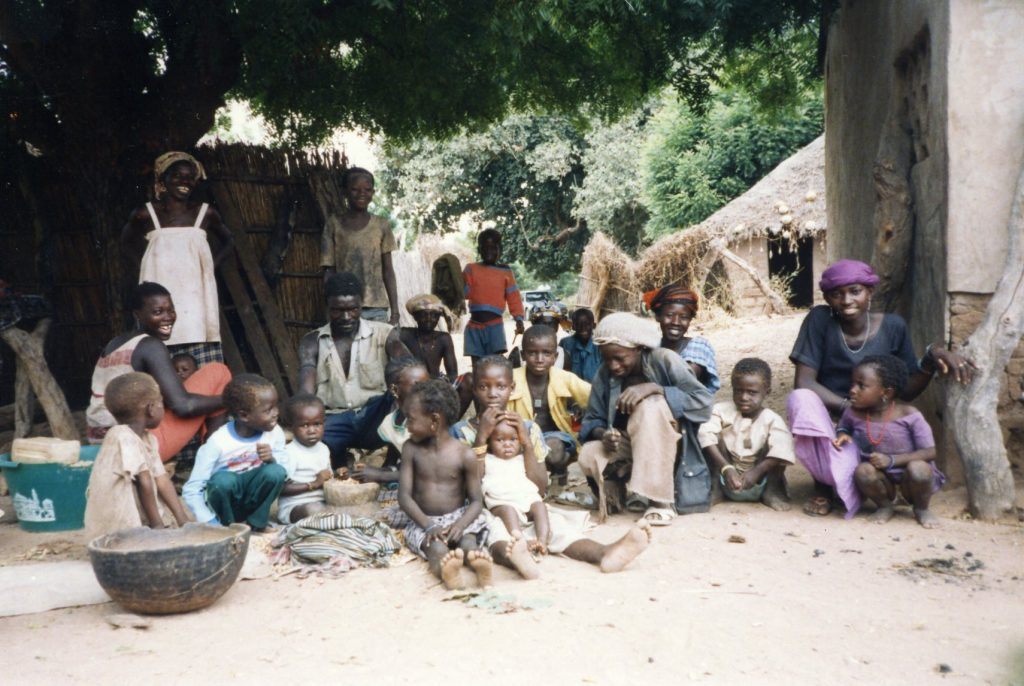 A group of small children and women sitting on the ground in a village in Senegal