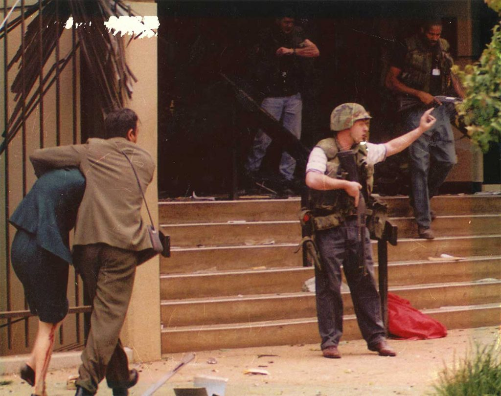 American military personnel holding a weapon signals while a man rushes with a woman towards the entryway